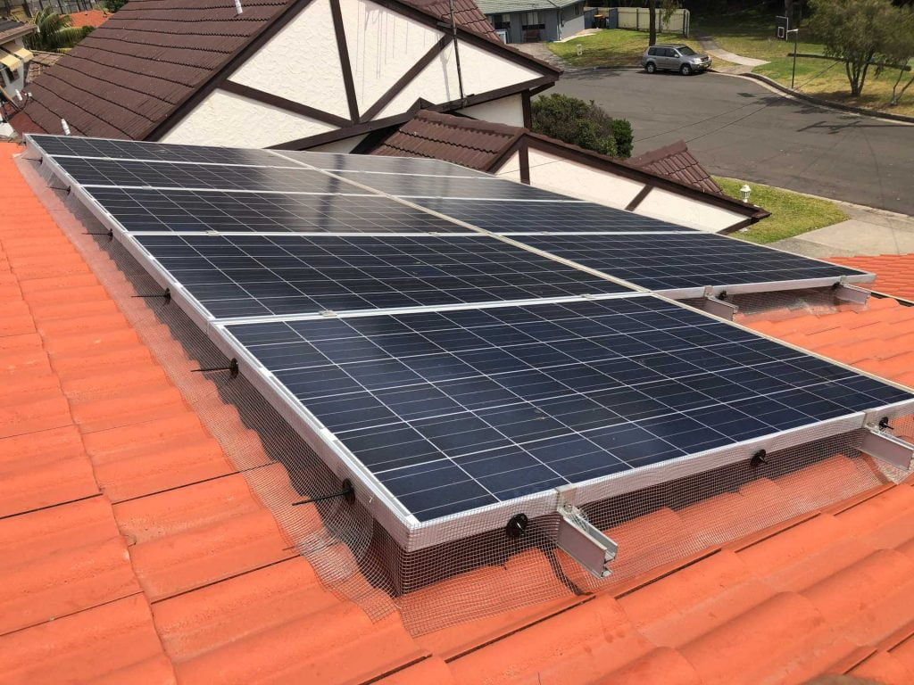 Mesh solar panel bird proofing on the terracotta-tiled roof of a Wollongong home